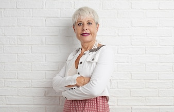 Senior cool woman against white brick wall background