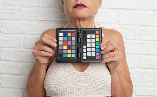 Senior cool woman with a gray card against white brick wall back