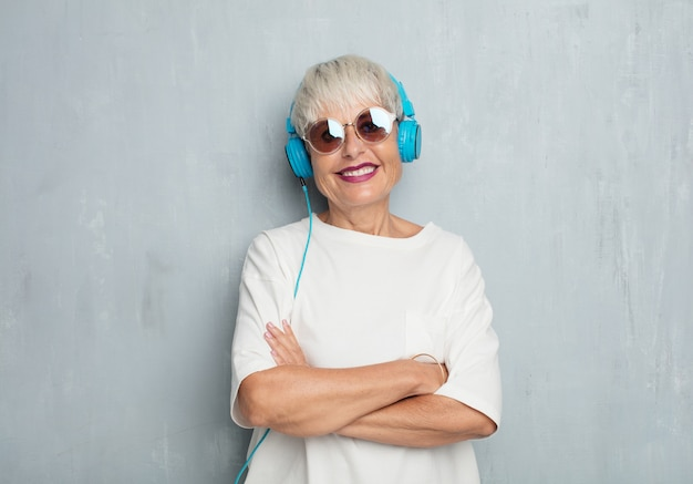 Senior cool woman with headphones, listening music against grung