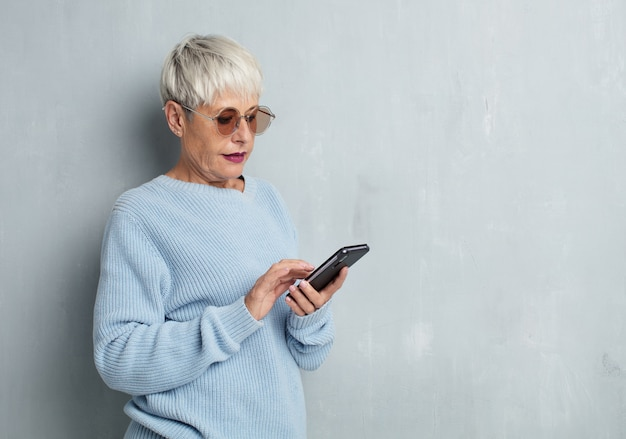 Senior cool woman  with a smart phone against grunge cement wall