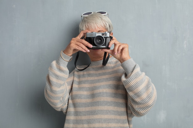 Senior cool woman with a vintage photography camera against grun