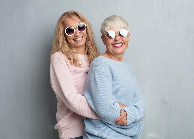 Senior cool women friends against grunge cement wall.