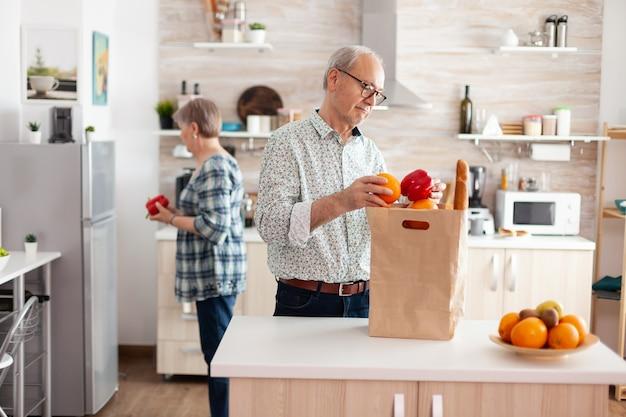 食料品の袋を持ってスーパーマーケットから到着し、早朝にキッチンで開梱する年配のカップル。一緒に時間を過ごし、助け合いながら人生を楽しむ高齢者退職者