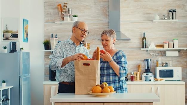 식료품 가방을 들고 슈퍼마켓에서 도착한 노인 부부는 부엌에서 포장을 풀고 있습니다. 삶을 즐기며 서로를 도우며 시간을 보내는 은퇴한 노인들