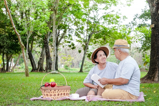 Senior couple, asian husband and wife sit and picnic and relax in the park.