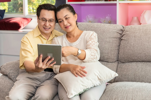 Senior couple asian retired looking tablet in nursing home.