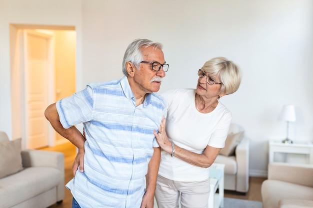 自宅の年配のカップル。老人は背中の痛みを抱えており、彼の恋人の妻は彼をサポートしています。