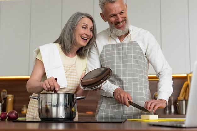 自宅の台所でノートパソコンで料理のレッスンを受ける老夫婦