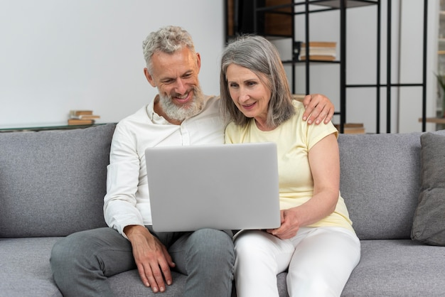 Старшая пара дома на диване, используя ноутбук