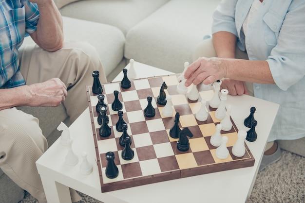 自宅で年配のカップルがチェスをする