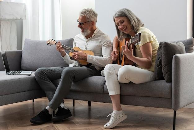 自宅でノートパソコンでギターとウクレレのレッスンを勉強している年配のカップル