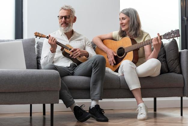 Старшая пара дома изучает уроки гитары и укулеле на ноутбуке