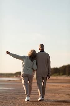 海辺のフルショットで年配のカップル