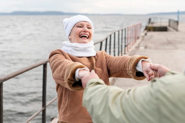 Пожилая пара на берегу моря спиннинг