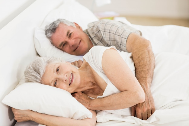 Senior couple in bed smiling at the camera