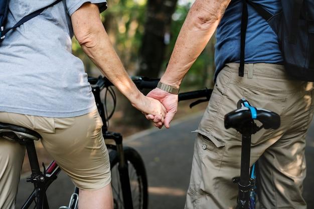 年配のカップルが公園でサイクリング