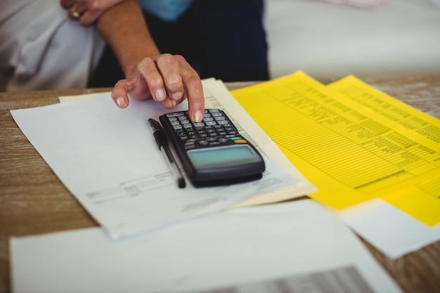 年配のカップルがリビングルームで請求書を計算します。