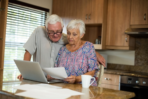Senior couple calculating their invoices with laptop in the kitchen at home