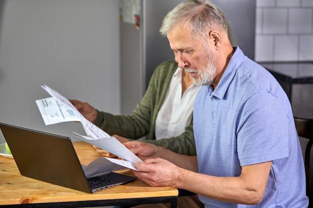 Старшая пара проверяет счета при управлении счетами в приложении домашнего банкинга. случайные седые мужчина и женщина с ноутбуком, глядя на счет-фактуру и планируют бюджет, чтобы сэкономить
