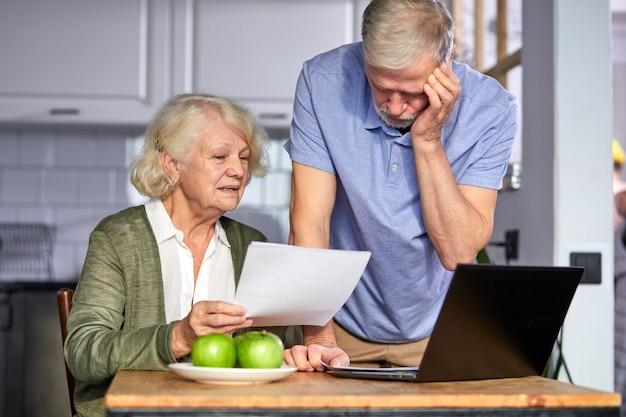 ホームバンキングアプリでアカウントを管理しながら請求書をチェックする年配のカップル。請求書を見ながらラップトップを使用して節約する予算を計画するカジュアルな白髪の男性と女性