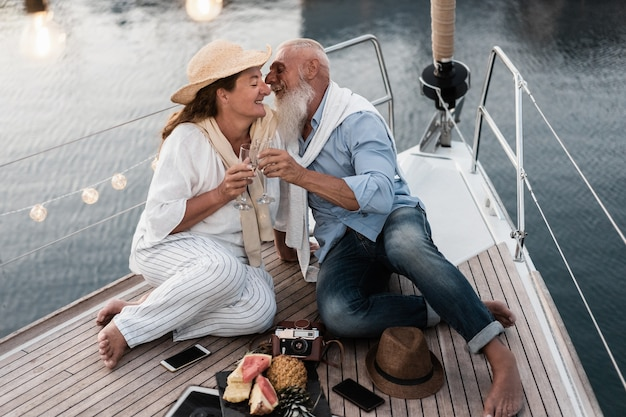 Senior couple cheering with champagne on sailboat during summer vacation - focus on man face