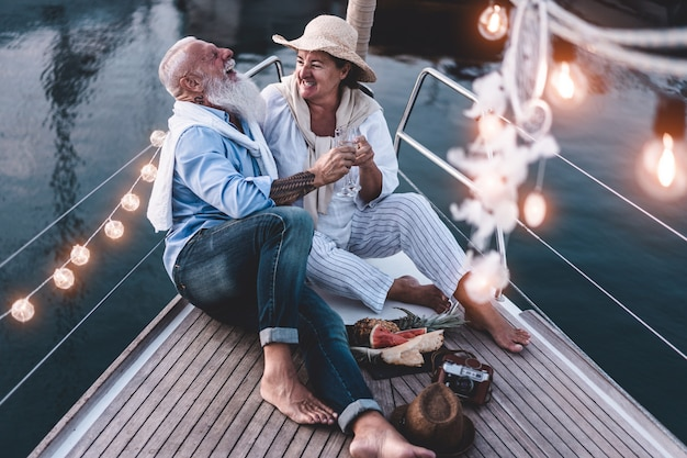 Senior couple cheering with champagne on a sailboat during summer vacation