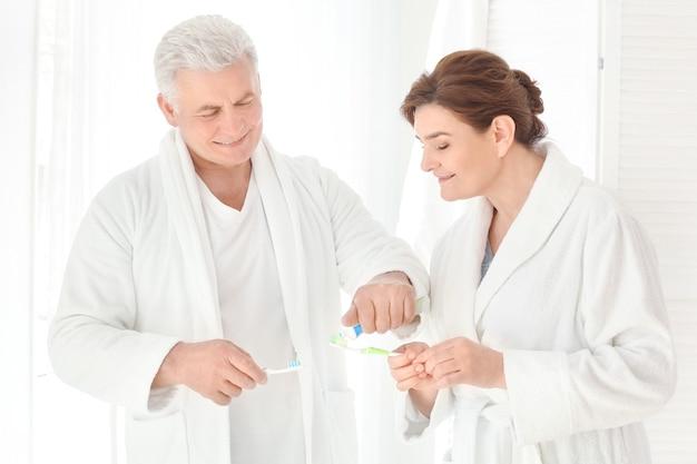 Старшая пара чистит зубы дома