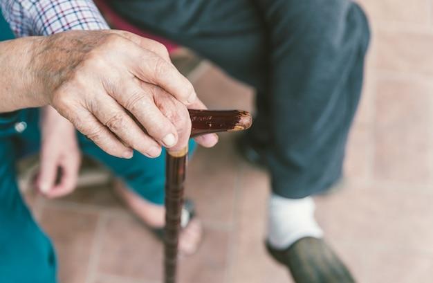 Старшие пары крупным планом. держа друг друга за руки на трость