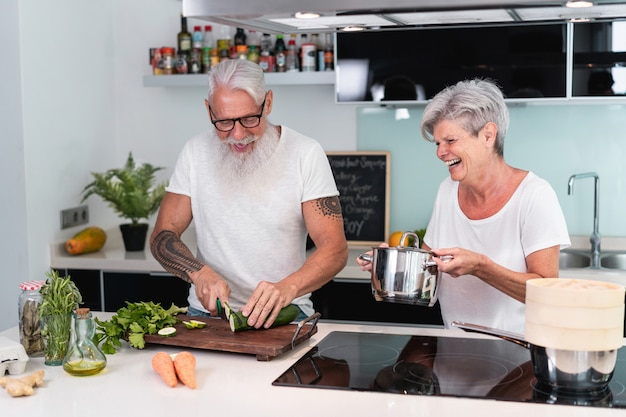 Senior couple cooking at home while preparing vegetarian lunch