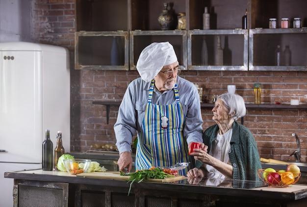 一緒に料理をする年配のカップル。男はシェフの帽子をかぶって新鮮な野菜を刻んでいます。健康的な食生活。