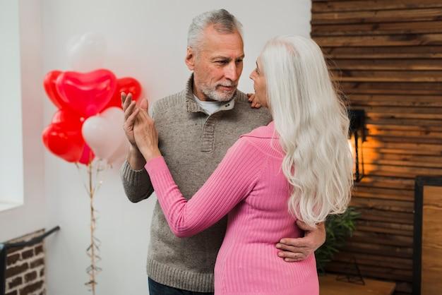 Пожилая пара танцует дома