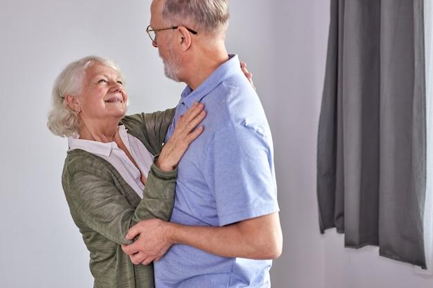 居間で踊る年配のカップル、一緒に楽しんでいる成熟した妻の手を握っている夫、休日を過ごす、家で余暇の退職のifestyle。カジュアルな家庭用ウェア