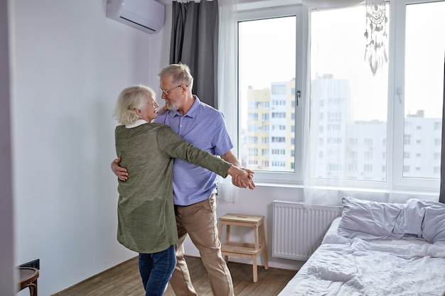 Senior couple dancing in living room, husband holding hand of mature wife enjoying fun together, spend holidays, leisure retirement ifestyle at home. in casual domestic wear