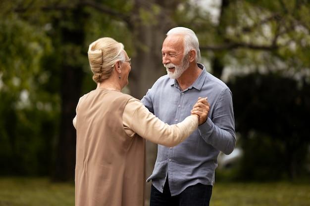 Senior couple dancing outside