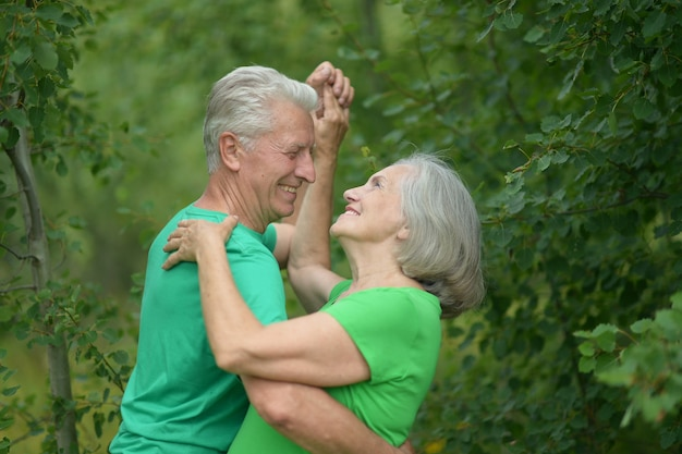 Senior couple dancing in a summer forest
