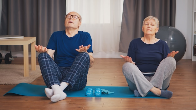 거실에 있는 요가 매트에서 호흡 운동을 하는 노인 부부. 집에서 노인 건강한 생활 방식 운동, 운동 및 훈련, 집에서 스포츠 활동