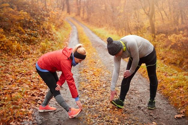 自然の中で運動をしている年配のカップル