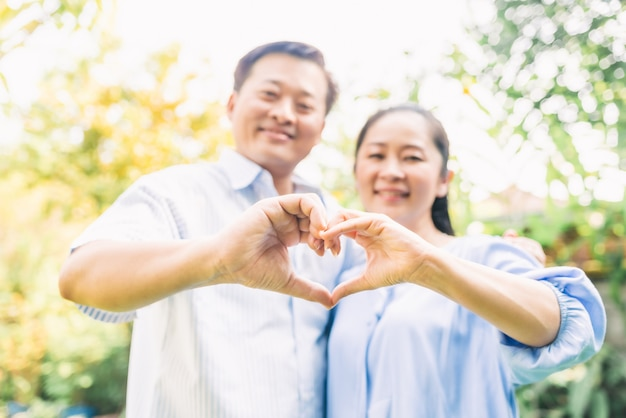 Senior couple doing heart shape gesture