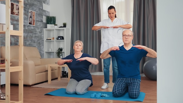 自宅で医師と理学療法をしている年配のカップル。在宅支援、理学療法、老人の健康的なライフスタイル、トレーニング、健康的なライフスタイル