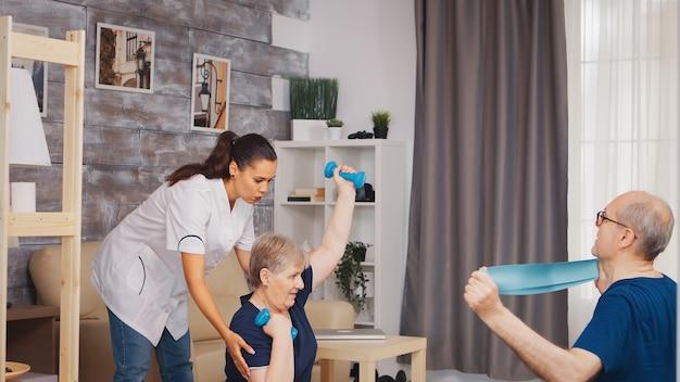 医者と理学療法をしている年配のカップル。在宅支援、理学療法、老人の健康的なライフスタイル、トレーニング、健康的なライフスタイル