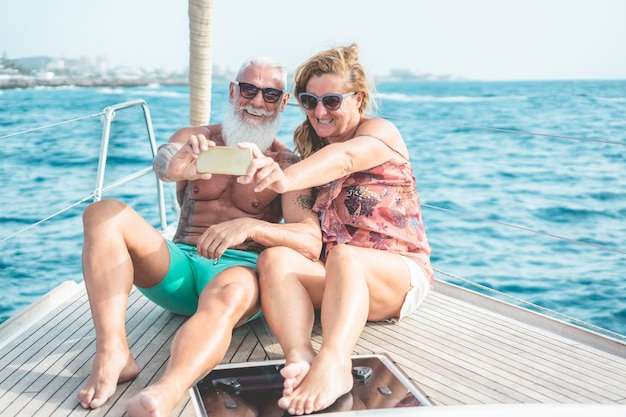 Senior couple doing selfie on sailboat during luxury ocean trip vacation