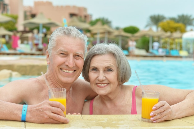 Senior couple drinking juice in pool at hotel resort