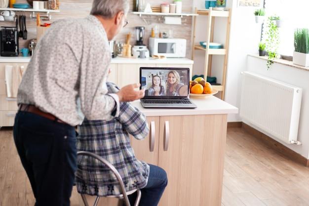 ラップトップを使用してキッチンで娘とのビデオ会議中の年配のカップル。熱狂的な祖父母が仮想ディスカッション中にウェブカメラを使用してオンラインで家族と話し、現代のコミュニケーションをオンラインで