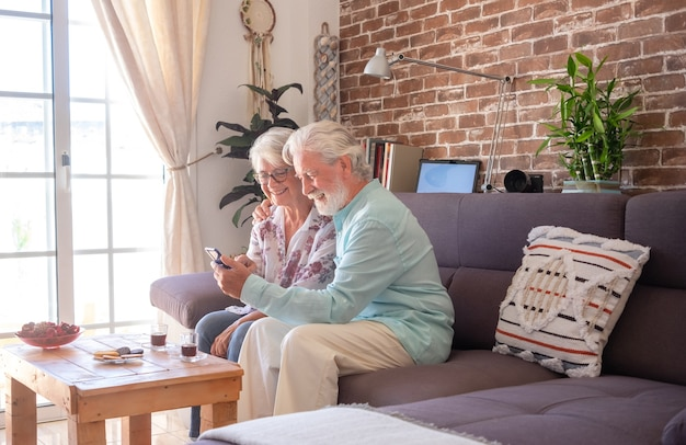 Senior couple embraced on sofa at home using mobile phone. brick wall on background