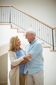 Пожилая пара, обнимая друг друга в гостиной