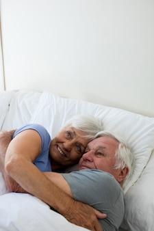 自宅の寝室で抱き合って抱き合う老夫婦