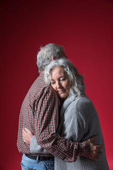 Senior couple embracing standing against red background