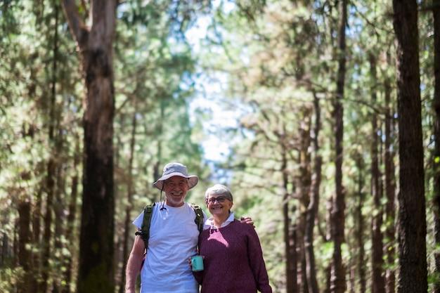 年配のカップルが一緒に森の中を歩くアウトドアレジャー活動を楽しむ