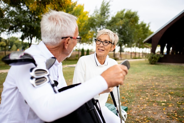 Старшие пары наслаждаются перерывом на тренировке в гольф.