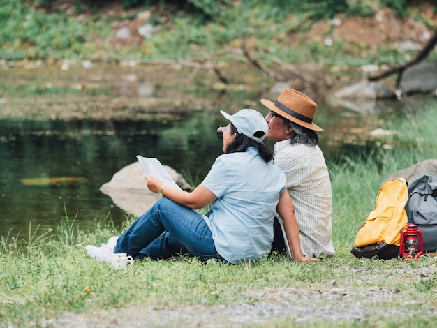 Senior couple enjoying camping trip, they drink coffee in the morning together.